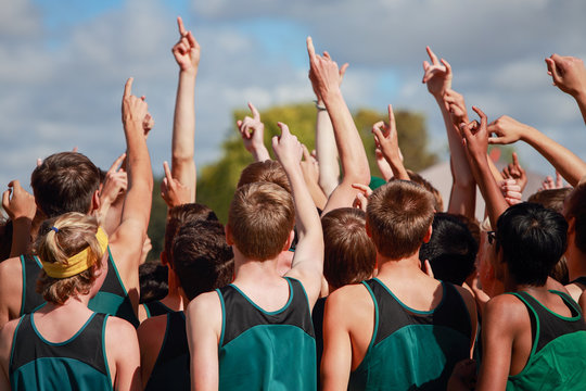 Boys on cross country team in a huddle raising arms pointing their fingers for number one