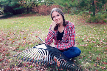 Woman sitting in the grass resting from raking leaves