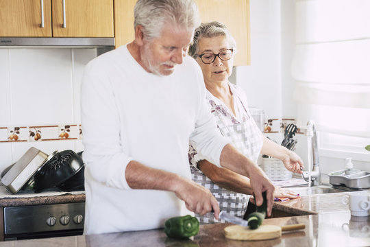 senior adult caucasian couple at home preparing dinner or lunch together. relationship and family lifestyle for people married in love. real people scene in the kitchen. together relationship forever