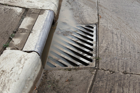 Stormwater filling a flooded sewer drain to the top
