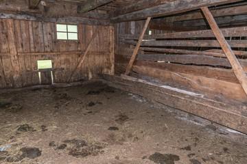 Innenaufnahme eines alten Kuhstall aus Holz auf einer Alm, Österreich