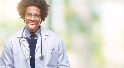 Afro american doctor man over isolated background sticking tongue out happy with funny expression. Emotion concept.