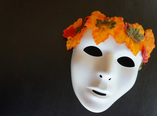 White spirit of autumn mask with colorful crown of leaves, black backdrop