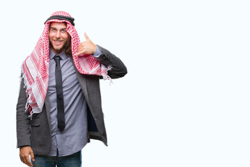 Young handsome arabian man with long hair wearing keffiyeh over isolated background smiling doing phone gesture with hand and fingers like talking on the telephone. Communicating concepts.