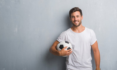 Handsome young man over grey grunge wall holding soccer football ball with a happy face standing and smiling with a confident smile showing teeth