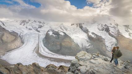 A couple of tourists enjoying the amazing glacier view in Gornergrat, Switzerland