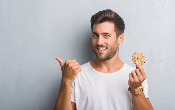 Handsome young man over grey grunge wall eating chocolate chip cooky pointing and showing with thumb up to the side with happy face smiling