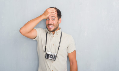 Handsome young man over grey grunge wall holding vintage photo camera stressed with hand on head, shocked with shame and surprise face, angry and frustrated. Fear and upset for mistake.