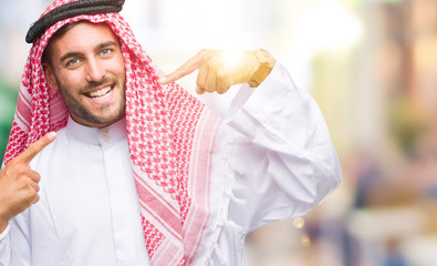 Young handsome man wearing keffiyeh over isolated background smiling confident showing and pointing with fingers teeth and mouth. Health concept.