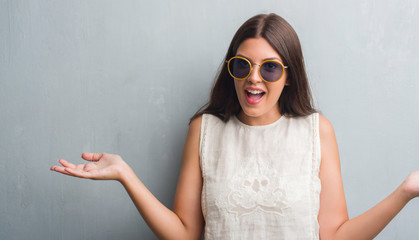 Young brunette woman over grunge grey wall wearing retro sunglasses very happy and excited, winner expression celebrating victory screaming with big smile and raised hands