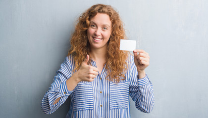 Young redhead woman over grey grunge wall holding blank visit card happy with big smile doing ok sign, thumb up with fingers, excellent sign