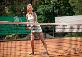 Smiling young female is standing on court in front of net. She is bending and holding racket with both hands while getting ready to hit. Copy space in right side