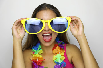 Girl ready for Carnival party. Young woman with big funny sunglasses and carnival garland smile at camera on gray background.