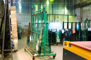 Warehouse at the plant for the production and processing of flat glass. Packs of ready-to-send glass are stored on the shelves