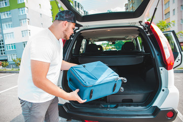 man putting bags in car trunk. ready for car travel
