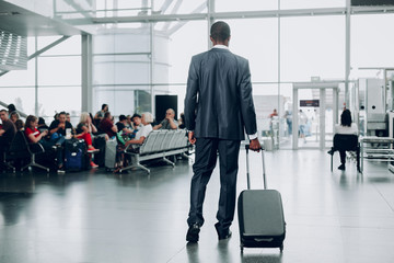 Waiting for plane. Full length portrait of man is standing back at waiting hall with his suitcase in anticipation of landing