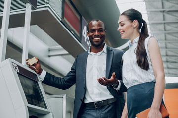 Ready for travel. Waist up portrait of two business partners are looking happy before the trip. They are holding gold card and tickets in their hands
