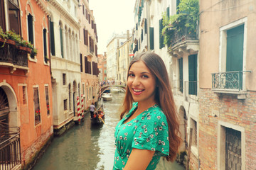 Holidays in Venice! Beautiful woman smiling at camera with Venice canal, gondolas and palaces on the background. Vintage filter.