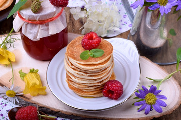 Stack of pancakes decorated with raspberry and mint on a white plate. Village style