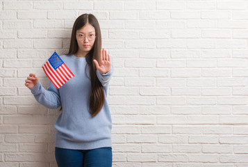 Young Chinese woman over brick wall holding flag of America with open hand doing stop sign with serious and confident expression, defense gesture