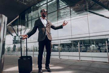 Happy about journey. Full length portrait of man during his business trip. He stands at the airport holding case and cup of coffee