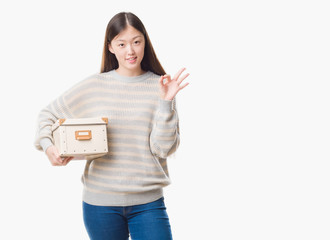 Young Chinese woman over isolated background holding a box doing ok sign with fingers, excellent symbol