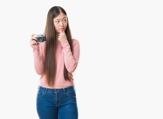 Young Chinese woman over isolated background taking pictures using vintage camera serious face thinking about question, very confused idea