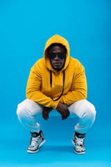 Street fashion. Studio portrait of young man in stylish yellow hoodie sitting on haunches and looking at camera with calm expression