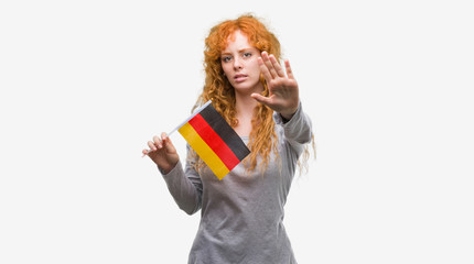 Young redhead woman holding flag of Germany with open hand doing stop sign with serious and confident expression, defense gesture