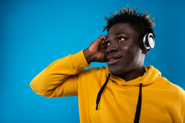 Feel the rhythm. Close up portrait of guy with headphones listening favorite song and looking up with smile. He is wearing stylish yellow sweatshirt and touching earphone. Copy space in left side