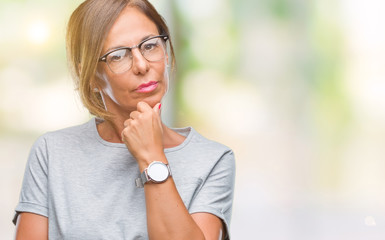 Middle age senior hispanic woman wearing glasses over isolated background looking confident at the camera with smile with crossed arms and hand raised on chin. Thinking positive.