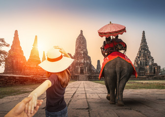 Tourists with an elephant at wat chaiwatthanaram temple in Ayutthaya Historical Park, a UNESCO world heritage site in Thailand, Couple travelers