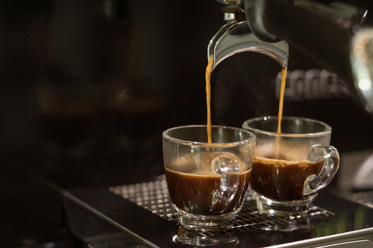 closed-up espresso machine brewing coffee in two shot glasses throgh portafilter
