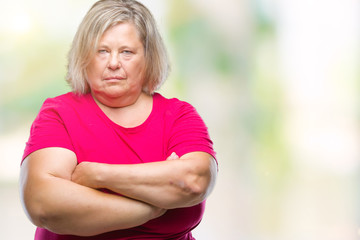 Senior plus size caucasian woman over isolated background skeptic and nervous, disapproving expression on face with crossed arms. Negative person.