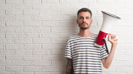 Young adult man holding megaphone with a confident expression on smart face thinking serious
