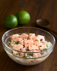 Chilean salmon ceviche prepared with onion, garlic, fresh coriander, salt and lemon juice, photographed with natural light (Selective Focus, Focus in the middle of the ceviche)