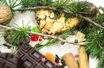 Cookies, tree branches, cinnamon, chocolate, cloves are on a white background