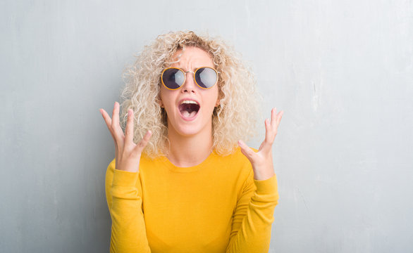 Young blonde woman with curly hair over grunge grey background crazy and mad shouting and yelling with aggressive expression and arms raised. Frustration concept.