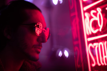 man with stubble and sunglasses looking at neon sign