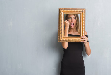 Beautiful young woman over grunge grey wall holding vintage frame annoyed and frustrated shouting with anger, crazy and yelling with raised hand, anger concept