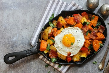 Skillet Breakfast Hash with potatoes bacon  peppers sweet potatoes and fried egg, top view
