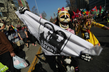 A demonstrator takes part in a march and protest ahead of the anniversary of the country's 1973 military coup on September 11, in Santiago