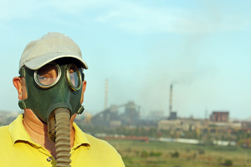 Men in gas mask looks at camera against the industrial factory and smoking pipes.