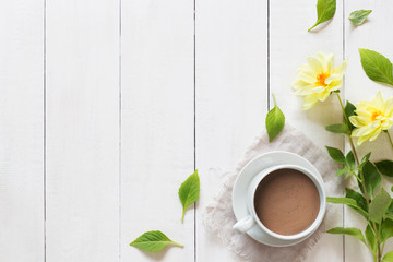 Cup of hot chocolate with flowers on wooden background