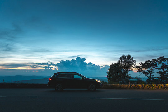 A black Subaru Outback is parked in front of an overlook in Shenandoah National Park, VA at sunset.