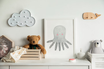 Stylish scandinavian newborn baby room with toys, teddy bears, wooden boxes and cloud. Modern interior with mock up photo frame.
