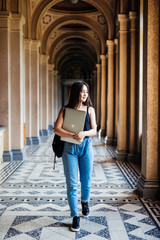 Young asian woman student holding laptop at college walking to the classes in university hall