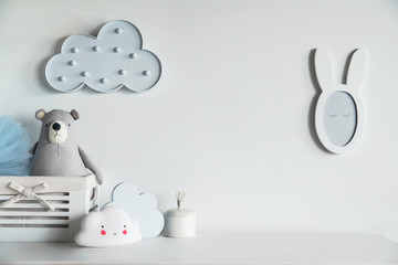 Stylish and cozy childroom with teddy bear, clouds and little mirror Bright and sunny interior.