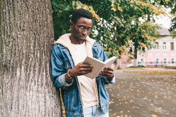 Wall Mural - Fashion african man reading book in autumn city park near tree