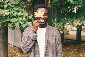 Happy smiling african man holds in hand yellow maple leaves, hides his eye in autumn day of city park